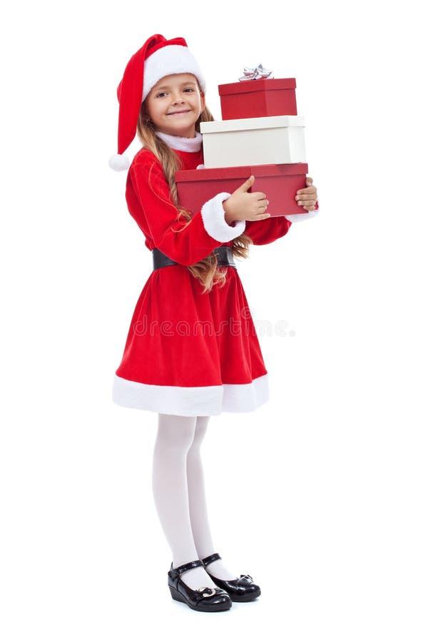 Menina feliz em presentes da terra arrendada do equipamento de Santa imagens de stock