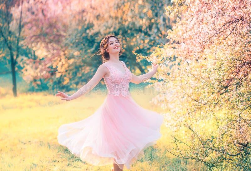 Menina feliz em risos cor-de-rosa delicados do vestido do voo curto alegremente, giros da princesa da boneca no jardim amarelo br imagem de stock royalty free