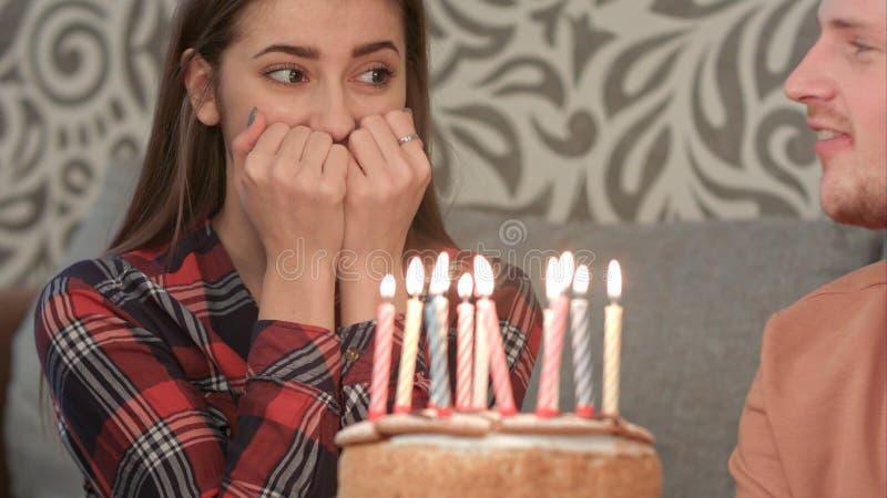 A menina feliz em seu aniversário faz um desejo e funde para fora as velas no bolo fotos de stock royalty free