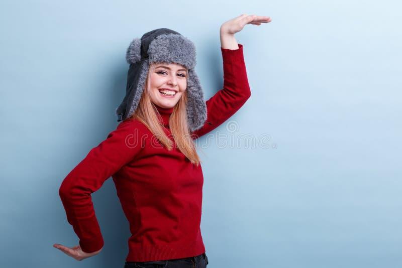 A menina feliz em um chapéu e em uma camiseta mornos, dança alegremente movendo suas mãos Em um fundo azul fotografia de stock