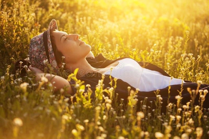 A menina feliz em um chapéu está encontrando-se entre flores selvagens e sonho imagens de stock royalty free