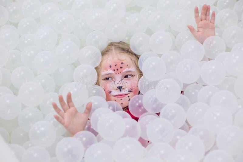 Menina feliz em uma sala de jogos em uma sala branca imagem de stock