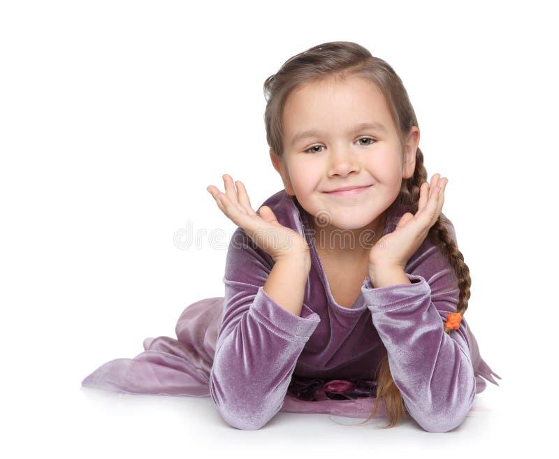 A menina feliz encontra-se no assoalho e no sorriso fotos de stock