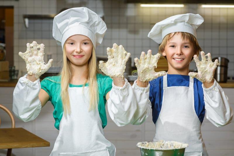 Menina feliz engraçada da largura do menino do cozinheiro chefe que cozinha em foto de stock