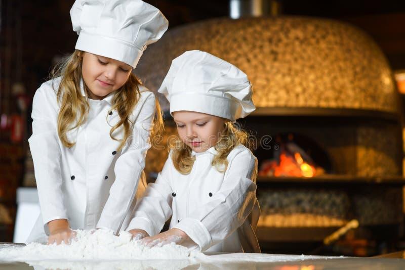 Menina feliz engraçada da largura do menino do cozinheiro chefe que cozinha em imagens de stock royalty free
