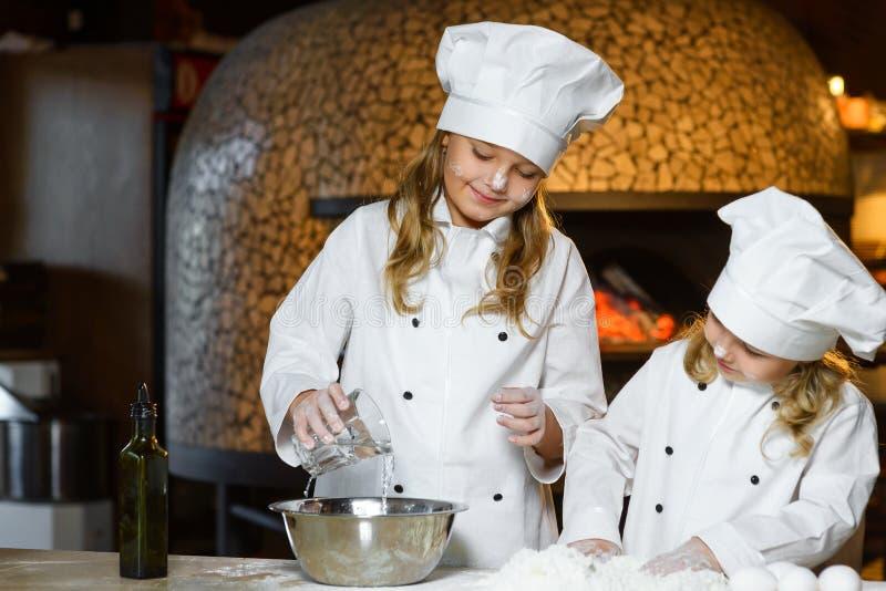 Menina feliz engraçada da largura do menino do cozinheiro chefe que cozinha em imagem de stock royalty free