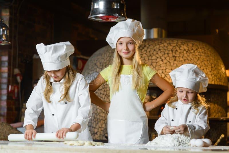 Menina feliz engraçada da largura do menino do cozinheiro chefe que cozinha em fotos de stock