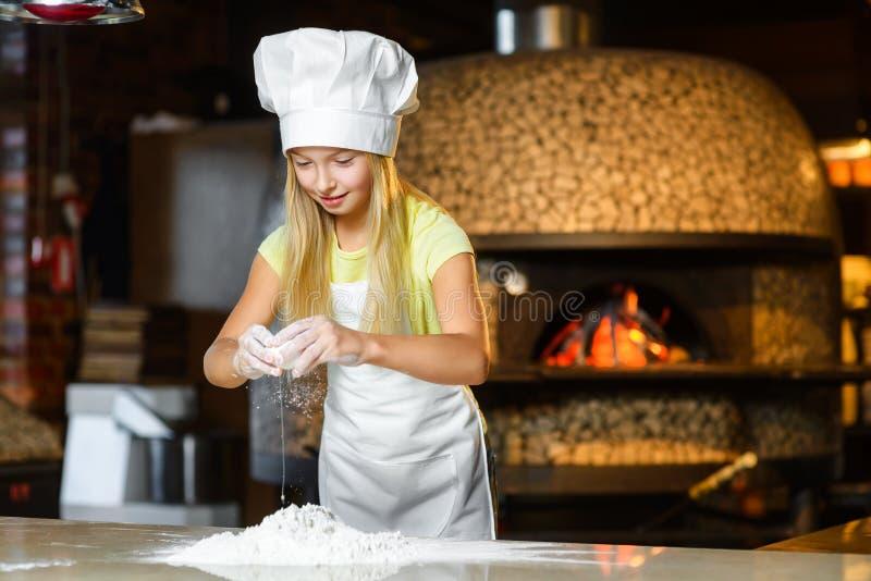 Menina feliz engraçada do cozinheiro chefe que cozinha no restaurante fotos de stock