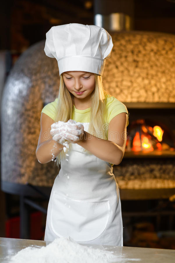 Menina feliz engraçada do cozinheiro chefe que cozinha no restaurante foto de stock royalty free