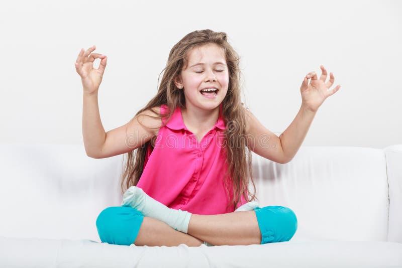 Menina feliz engraçada que senta-se em meditar do sofá fotos de stock
