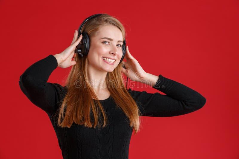 Menina feliz, escuta de sorriso a música em fones de ouvido Em um fundo vermelho foto de stock