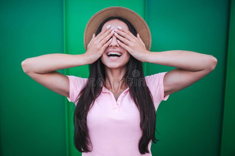 A menina feliz está e mantém seus olhos fechados com mãos Está sorrindo A morena veste o chapéu cor-de-rosa da camisa e de palha fotos de stock