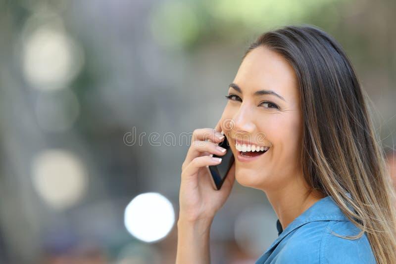 A menina feliz fala no telefone na rua que olha o imagem de stock
