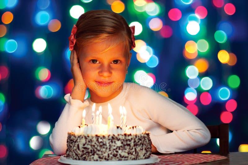 A menina feliz funde para fora as velas no bolo fotografia de stock