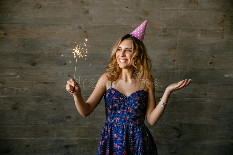 A menina feliz guarda a luz de bengal ao comemorar um partido fotografia de stock royalty free