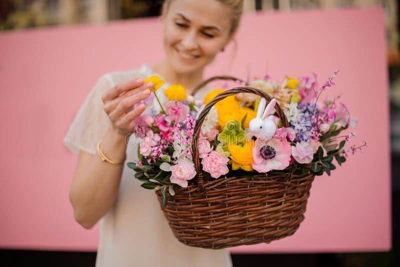 A menina feliz guarda o ramalhete na cesta da flor fotos de stock royalty free
