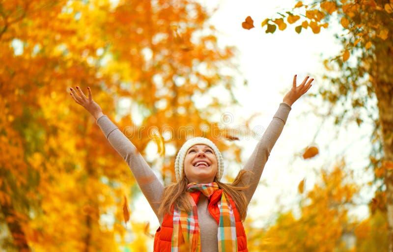 A menina feliz joga acima as folhas de outono no parque para a caminhada fora fotografia de stock
