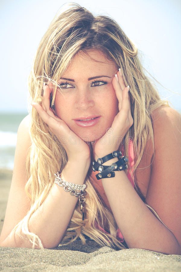 Menina feliz loura de sorriso no mar que encontra-se na praia Duas mãos sob sua cara imagens de stock