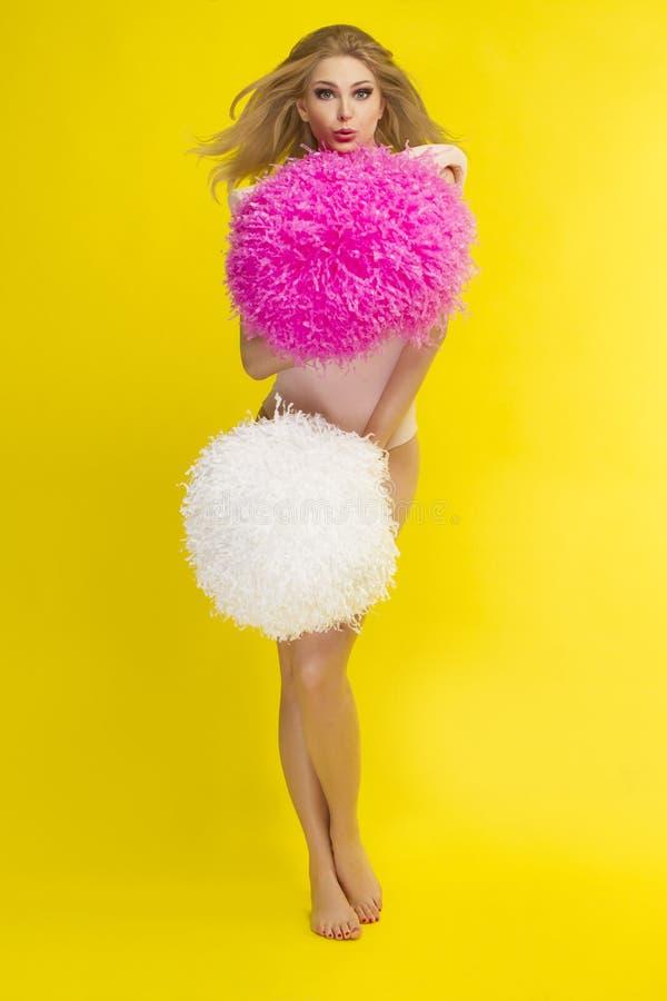 Menina feliz loura que cheering com pom do pom, fundo amarelo fotografia de stock royalty free