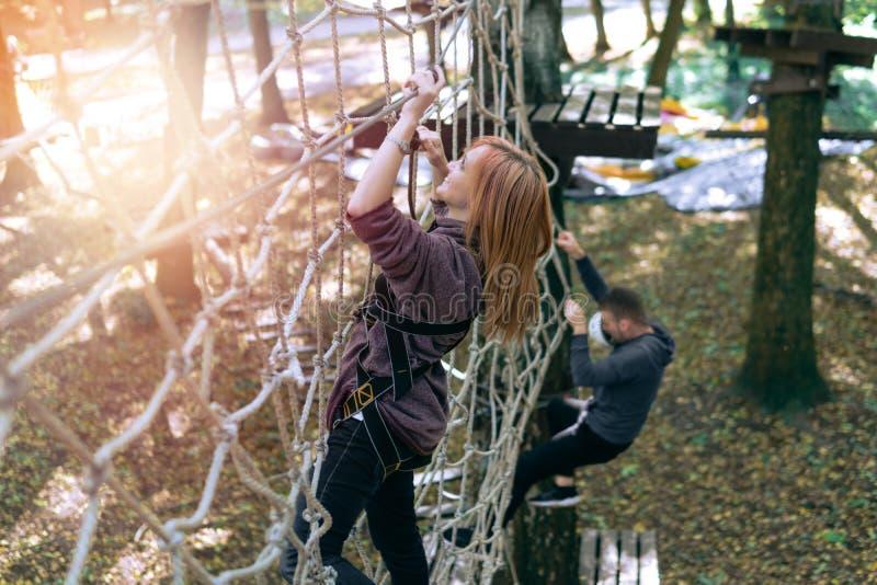 Menina feliz, mulher, engrenagem de escalada em uma aventura, estrada da corda, seguro, atração, parque de diversões, recreação a imagem de stock royalty free