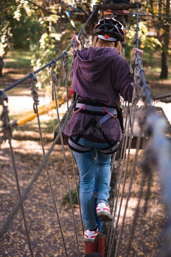 A menina feliz, mulheres, engrenagem de escalada em um parque da aventura é contratada na escalada na estrada da corda, arboreto, imagem de stock royalty free