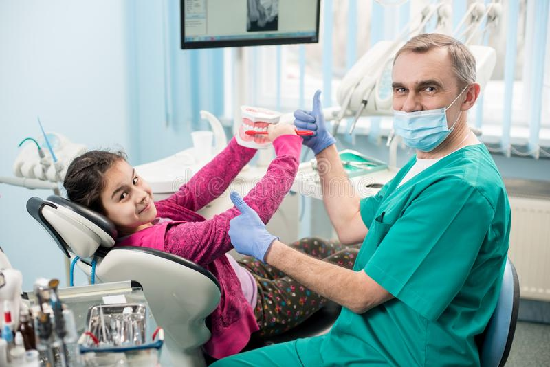 Menina feliz na cadeira do dentista que educa a dente-escovadela apropriada, usando o modelo da maxila e a escova de dentes denta fotografia de stock