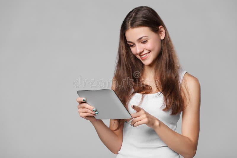 Menina feliz na camisa branca usando a tabuleta Mulher de sorriso com o PC da tabuleta, isolado no fundo cinzento fotografia de stock