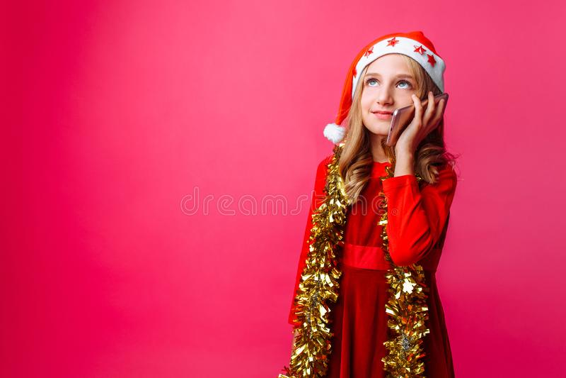 Menina feliz na capa de equitação vermelha do ` s de Santa e com ouropel em seu nec imagens de stock