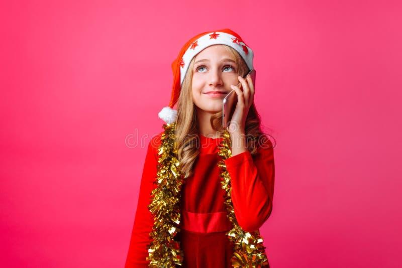 Menina feliz na capa de equitação vermelha do ` s de Santa e com ouropel em seu nec fotos de stock royalty free