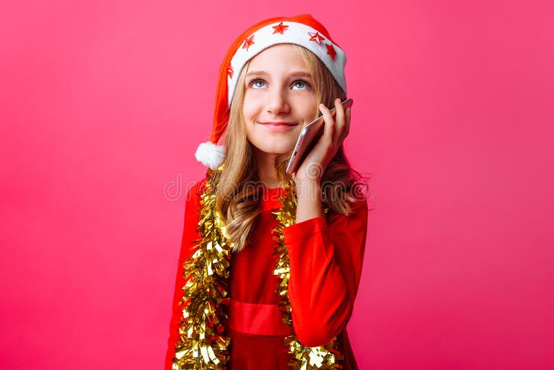 Menina feliz na capa de equitação vermelha do ` s de Santa e com ouropel em seu nec fotos de stock