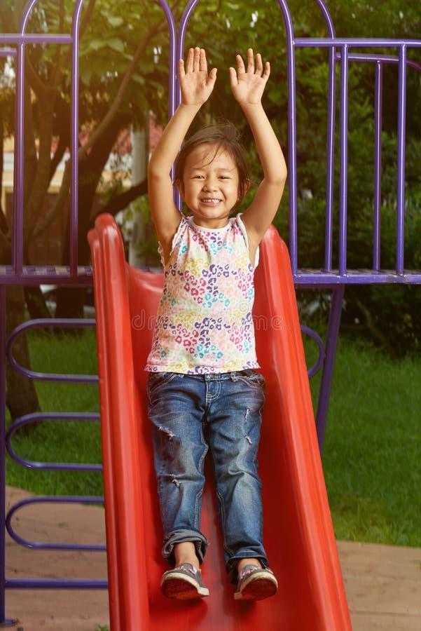 Menina feliz na corrediça do parque fotos de stock