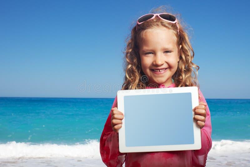Menina feliz na praia com PC da tabuleta foto de stock royalty free