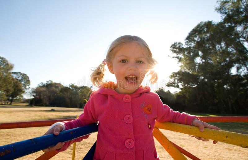 Menina feliz na terra do jogo do parque fotos de stock