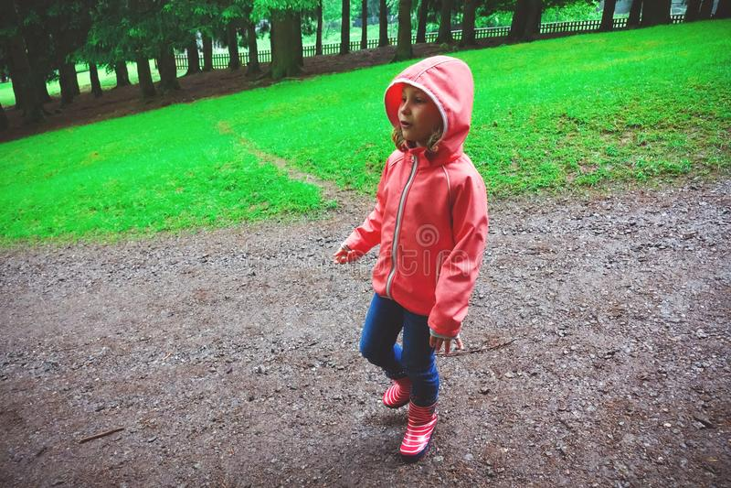 A menina feliz nas botas de borracha anda no parque natural e no lookin fotografia de stock