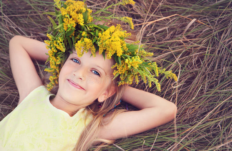 A menina feliz nas flores coroa a colocação na grama fotografia de stock