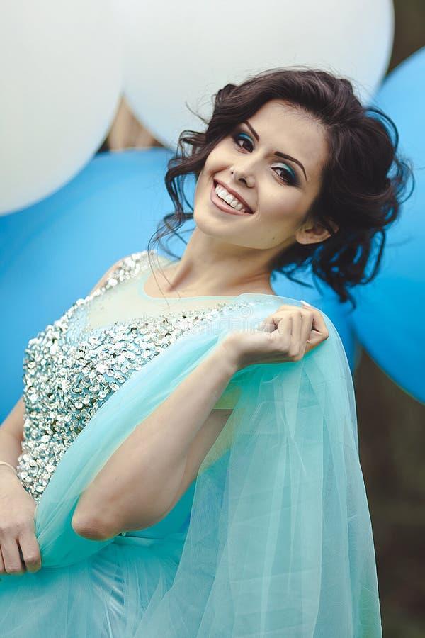 Menina feliz no baile de finalistas com os balões de ar do hélio Retrato de um graduado bonito da menina em um vestido azul Menin imagens de stock royalty free