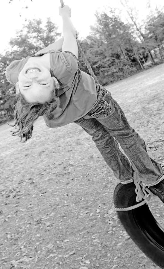 Menina feliz no balanço do pneu fotografia de stock royalty free
