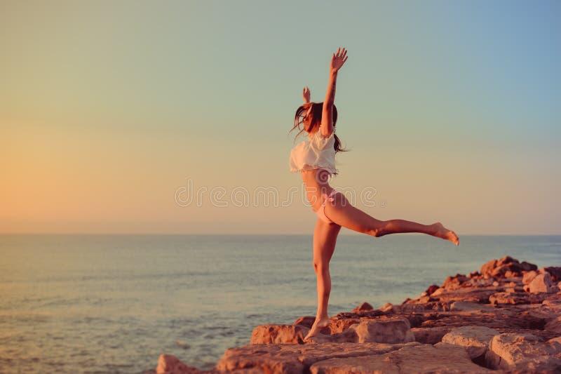 Menina feliz no biquini que salta em uma praia no por do sol ou no nascer do sol fotografia de stock