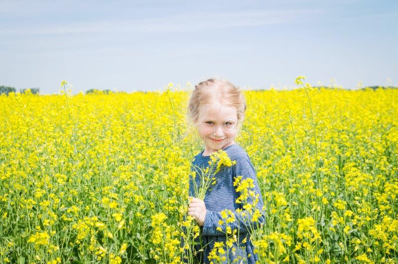 Menina feliz no campo de florescência da colza no verão fotografia de stock