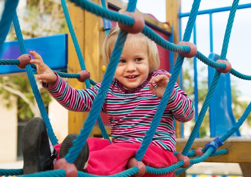 Menina feliz no campo de jogos ação-orientado foto de stock royalty free