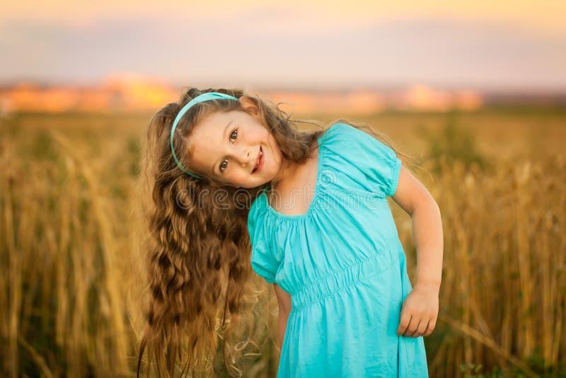 Menina feliz no campo de trigo na noite morna e ensolarada do verão imagem de stock