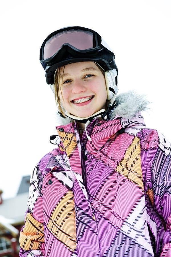 Menina feliz no capacete do esqui no recurso do inverno fotografia de stock royalty free