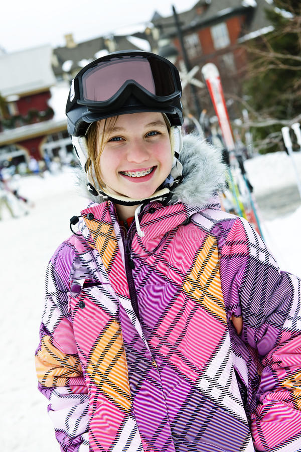 Menina feliz no capacete do esqui no recurso do inverno imagem de stock royalty free