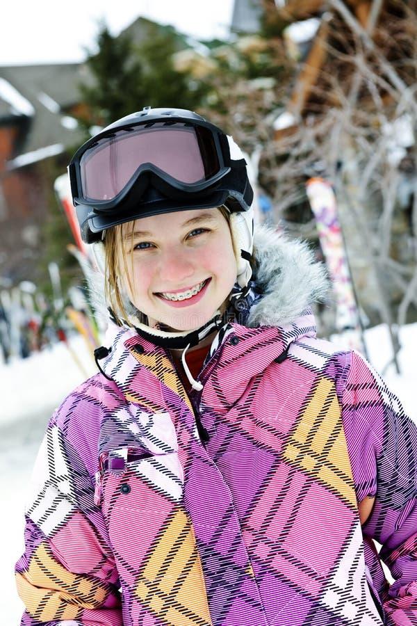 Menina feliz no capacete do esqui no recurso do inverno fotografia de stock
