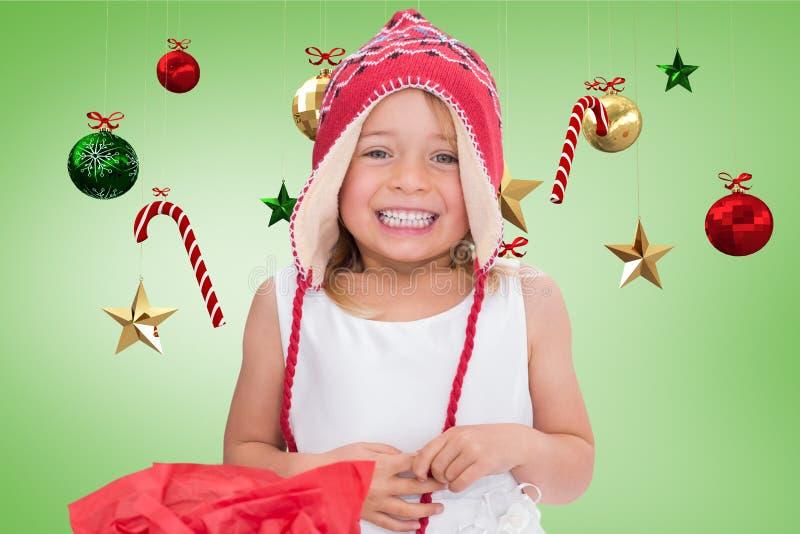 Menina feliz no chapéu de lã feito malha que sorri contra a decoração digitalmente gerada do Natal fotografia de stock royalty free