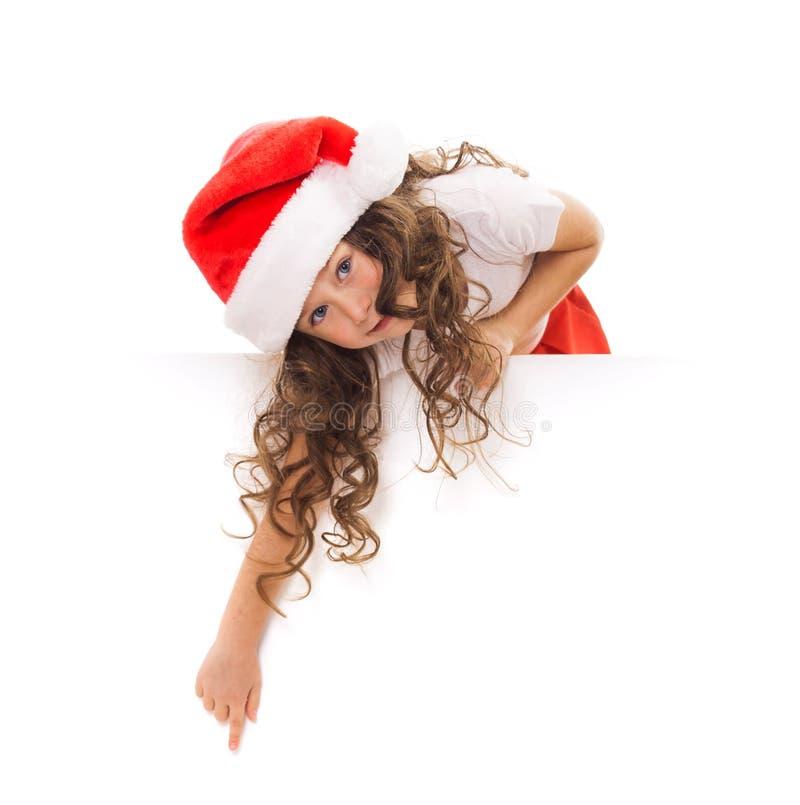 Menina feliz no chapéu de Santa que espreita de atrás fotos de stock royalty free