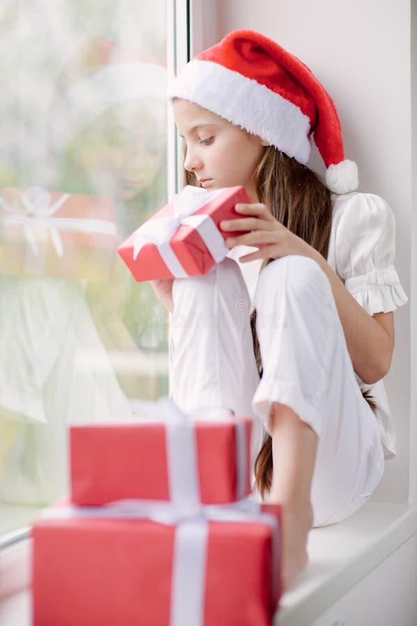 Menina feliz no chapéu de Santa que sonha pela janela que guarda o soldado foto de stock