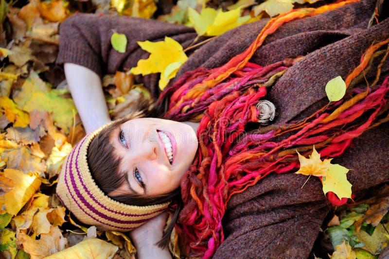 Menina feliz no chapéu feito malha que encontra-se nas folhas de outono foto de stock royalty free