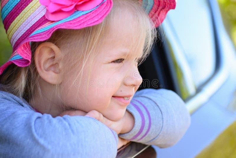 Menina feliz no tampão colorido brilhante que olha para fora a janela do carro e do sorriso fotos de stock
