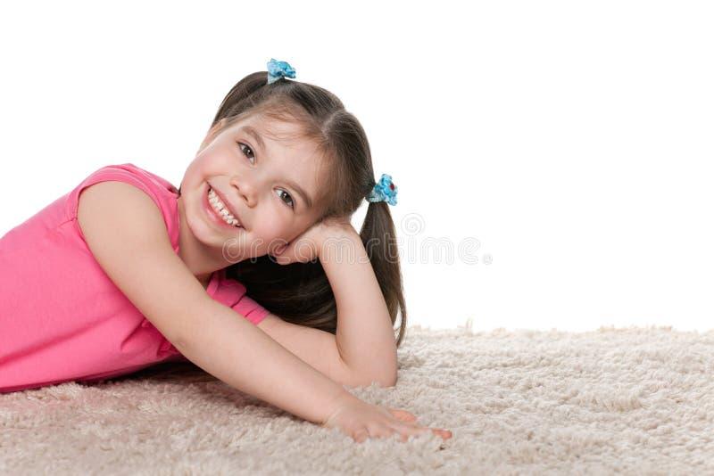 Menina feliz no tapete branco foto de stock